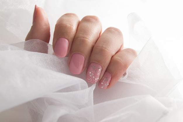 Verniz rosa suave e brilhos nas unhas - manicure com revestimento de salão de verniz em gel.