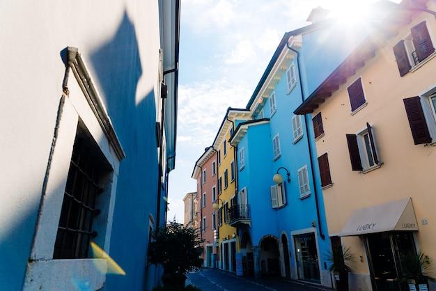 Verona, itália - 21 de setembro de 2021: bela rua de uma pequena aldeia italiana com casas coloridas com raios de sol.