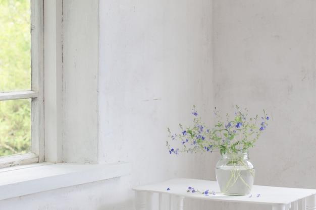 Veronica flores silvestres em jar no interior vintage branco