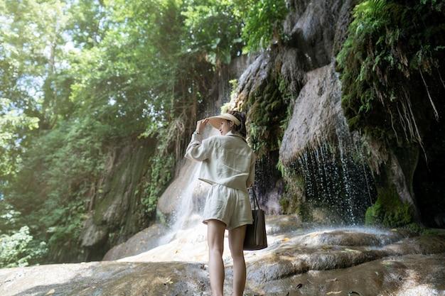 Verso da mulher com cachoeira na floresta tropical com pedra cachoeira saiyok noi