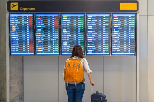 Verso de mochileiro ou viajante asiática com bagagem em pé sobre a placa de voo