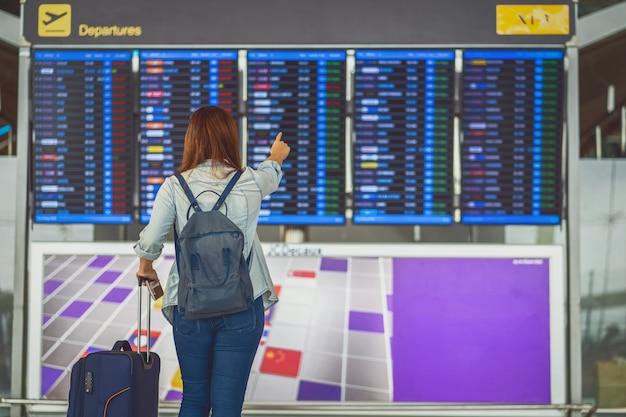 Verso de uma viajante asiática com bagagem em pé sobre a placa do voo para check-in
