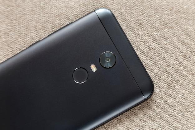 Verso do celular preto isolado com dispositivo de digitalização de impressão digital de polegar de segurança, câmera e iluminação flash na luz pano cópia espaço fundo
