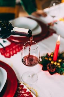 Vertendo vinho tinto no copo sobre uma mesa para o natal