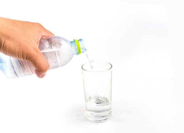 Verter a água em um copo no fundo branco