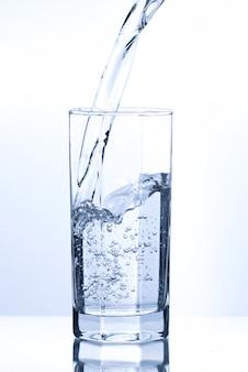 Verter água transparente em vidro com bolhas