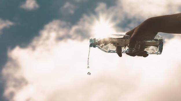 Verter uma garrafa de plástico transparente com água potável