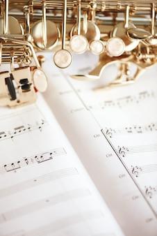 Vertical close-up imagem de teclas de saxofone deitado sobre as notas musicais. instrumentos musicais.