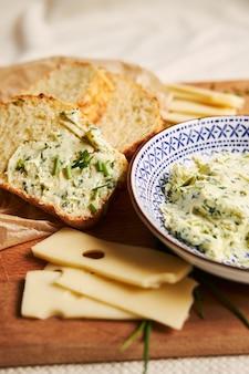 Vertical de fatias de pão de queijo com manteiga de ervas em uma mesa