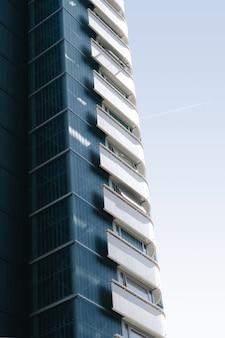 Vertical de um edifício de vidro com varandas brancas sob o céu azul