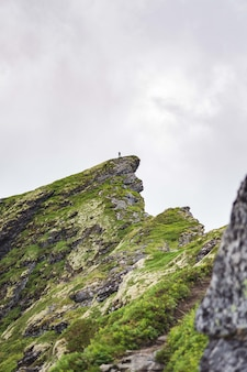 Vertical de uma rocha verde perto da vila reinebringen das ilhas lofoten