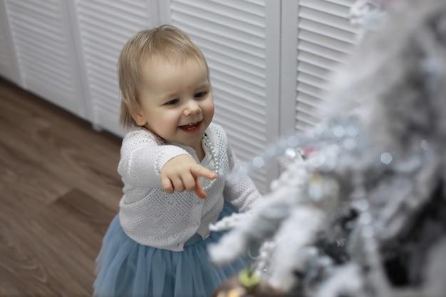 Véspera de ano novo. a casa está decorada para o feriado. árvore de natal elegantemente vestida com uma guirlanda e uma família com presentes e uma surpresa.