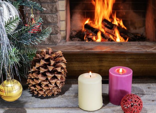 Véspera de natal. árvore de natal, velas, cones e brinquedos em frente a uma aconchegante lareira.