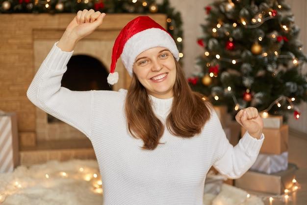 Véspera de natal. mulher feliz com as mãos para cima dançando alegremente com um sorriso, senhora de suéter e chapéu de papai noel vermelho, posando na sala de estar decorada com festão e árvore de natal.