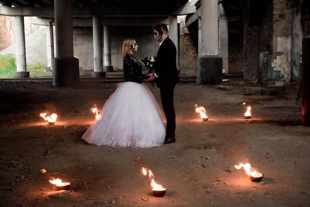 Vestida com roupas de casamento casal zumbi romântico.