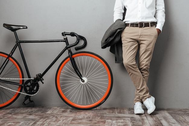 Vestida metade do corpo dos homens em pé perto de uma bicicleta