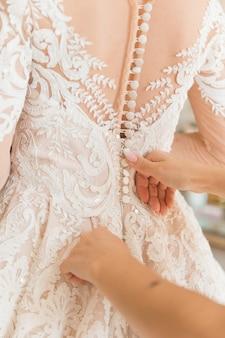 Vestido branco da noiva que é ajudada a abotoar pela dama de honra