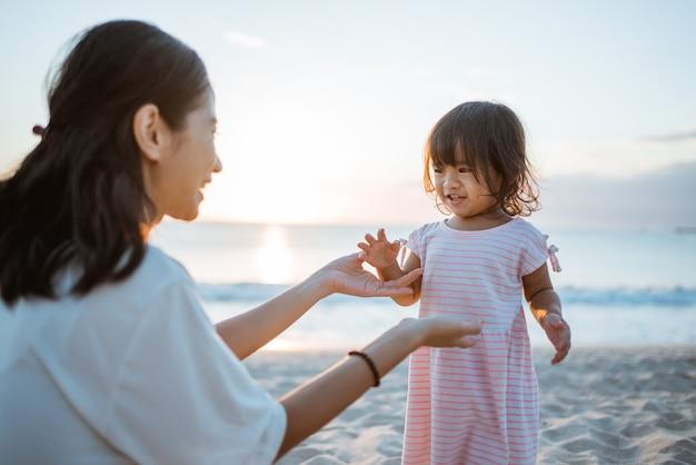 Vestido branco de menina em pé em uma praia de verão brincando com a mãe