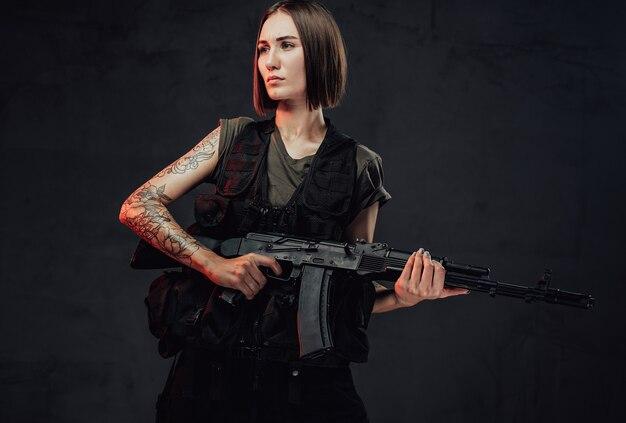 Vestido com uma armadura escura, mulher militar com corte de cabelo curto e mão enfaixada segura seu rifle de assalto em fundo esfumaçado escuro.