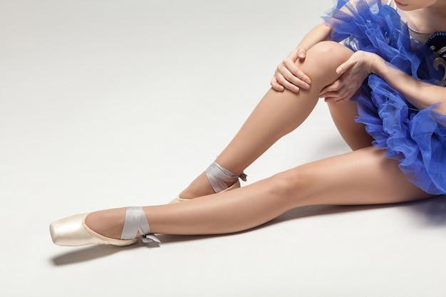 Vestido de bailarina azul com dor no joelho e sapatilhas de ponta sentada no chão branco, closeup