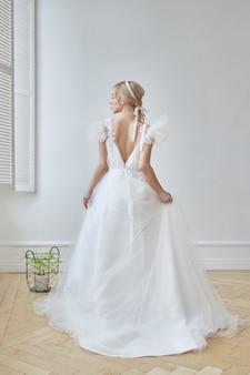 Vestido de casamento branco luxuoso no corpo da menina. nova coleção de vestidos de noiva. noiva de manhã, uma mulher esperando o noivo antes da cerimônia de casamento. jovem noiva em um vestido longo
