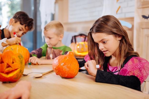 Vestido de halloween. linda garota de cabelos escuros usando um vestido rosa e preto para o dia das bruxas se divertindo enquanto tinge