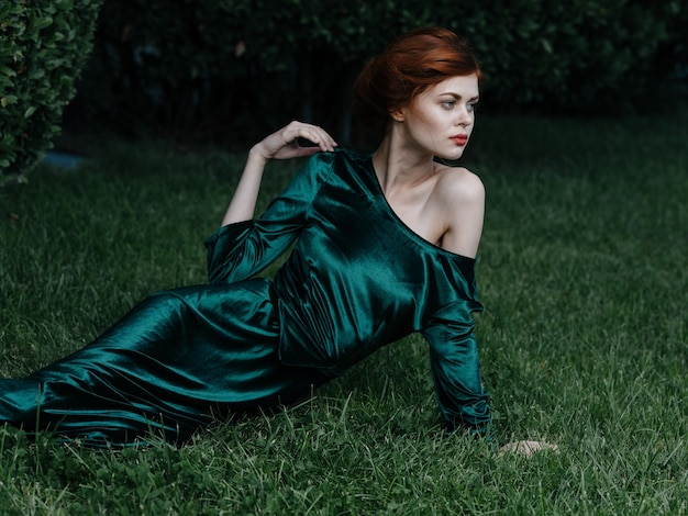 Vestido de mulher de luxo verde encontra-se no carnaval de princesa de grama.
