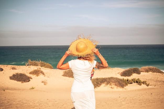 Vestido de mulher inwhite e chapéu visto de volta na praia.