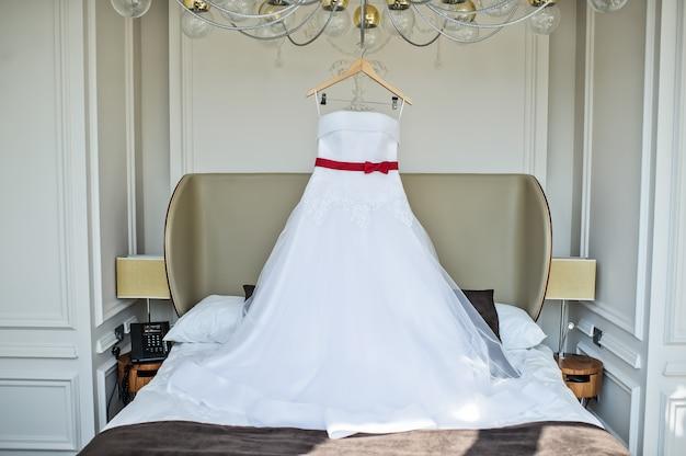 Vestido de noiva branco da noiva pendurado no lustre no quarto do hotel