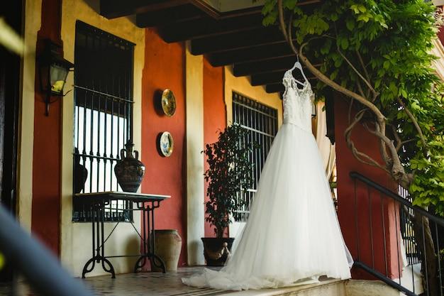 Vestido de noiva branco elegante e limpo, ninguém, pendurado em uma árvore no dia do casamento esperando