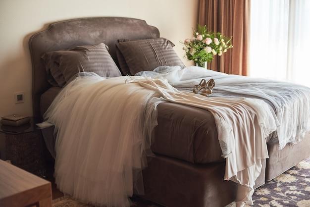 Vestido de noiva branco elegante, véu e sapatos deitado na cama.