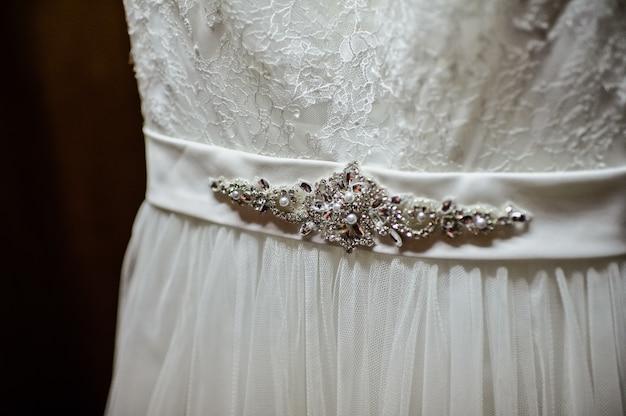 Vestido de noiva branco pendurado em um armário de madeira