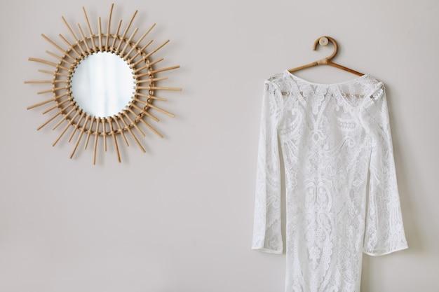 Vestido de noiva branco pendurado no quarto ao lado do espelho