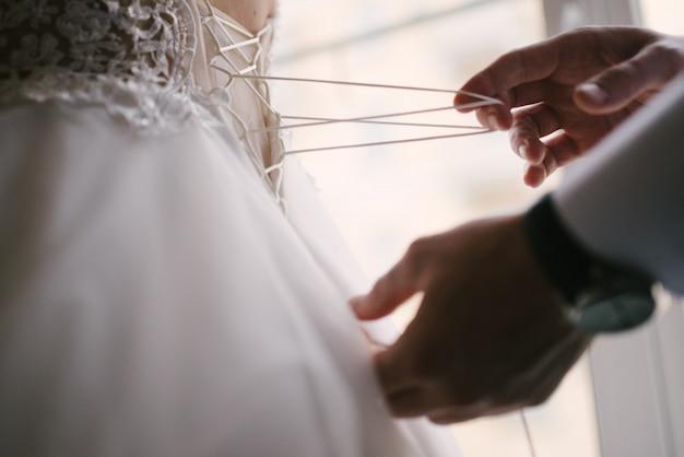 Vestido de noiva de renda branca de noiva. noiva ajuda colocar o vestido de noiva