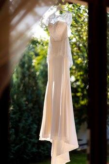 Vestido de noiva elegante pendurado em um galho