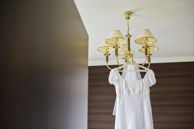 Vestido de noiva elegante pendurado no lustre no interior do hotel