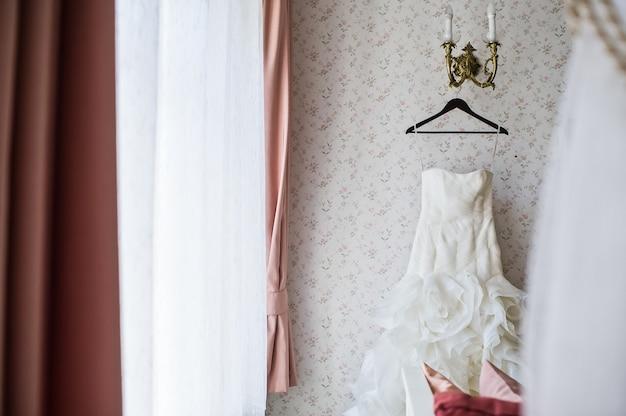 Vestido de noiva em um cabide no interior elegante do hotel