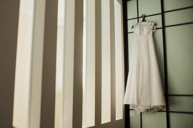 Vestido de noiva em um cabide perto da parede