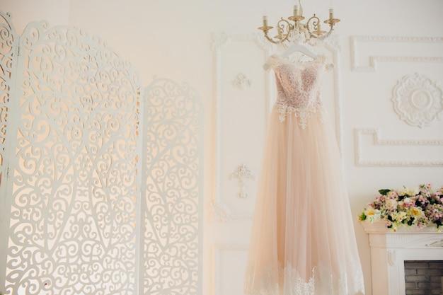 Vestido de noiva pendurado no brilho no quarto de hotel.