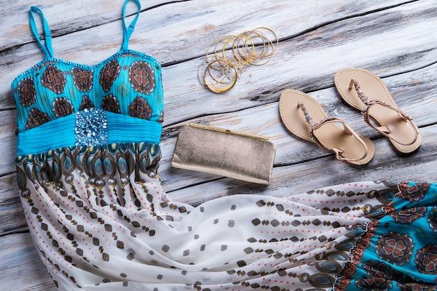 Vestido e sandálias bege. bolsa clutch e pulseiras em prata. seleção de roupas em boutique. melhor mercadoria em exposição.