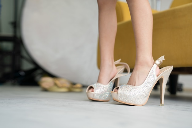 Vestido elegante usando sapatos grandes da mãe