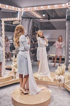 Vestido especial. comprimento total de mulheres jovens e atraentes experimentando um vestido de noiva enquanto passam um tempo na loja de noivas com a namorada