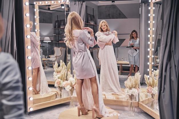 Vestido incrível. comprimento total de mulheres jovens e atraentes experimentando um vestido de noiva enquanto passam um tempo na loja de noivas com a namorada
