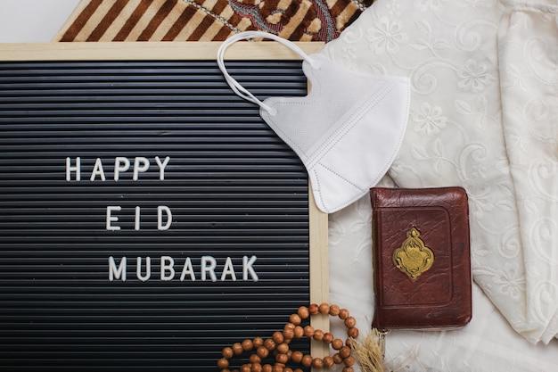 Vestido muçulmano chamado mukena e contas de oração com livro sagrado de al quran e quadro de correio diz happy eid mubarak no tapete de oração com máscaras de proteção. há uma palavra árabe que significa livro sagrado