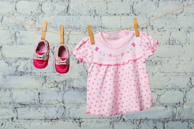 Vestido rosa bebê e sapatos vermelhos para a menina, seque com uma corda contra uma parede de tijolos brancos.