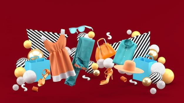 Vestidos, calças, moletons, chapéus, bolsas, sapatos de salto altos e óculos de sol entre bolas coloridas em vermelho. renderização em 3d.