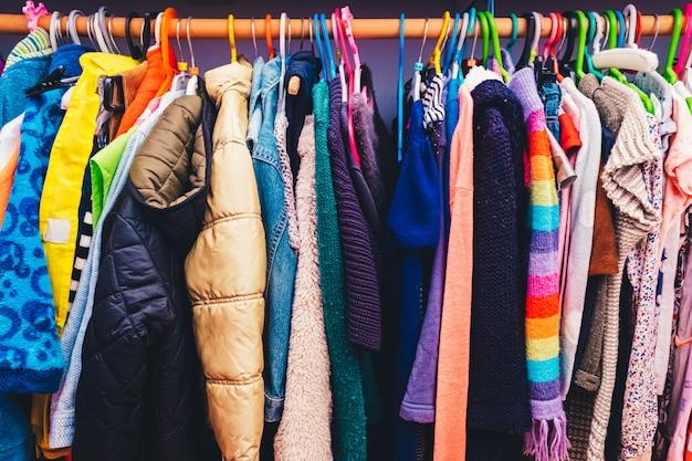 Vestidos coloridos para crianças pendurados em cabides no armário.
