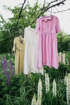 Vestidos de cores naturais pendurados em uma árvore no jardim com flores de tremoço