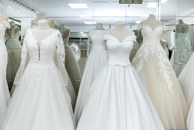 Vestidos de noiva da moda em cabide e manequins no salão