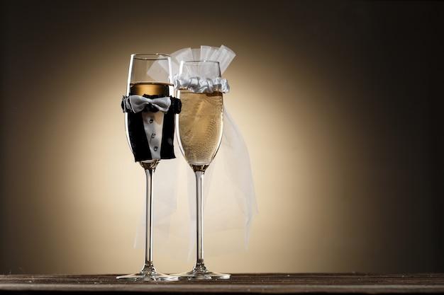 Vestidos em trajes de casamento, taças de champanhe